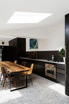 white terrazzo floor contrasts with black kitchen cabinets and stained wood furniture