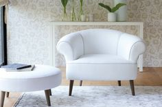 Designers Guild furniture showing off it's clean cut lines in a glistening white armchair and stool