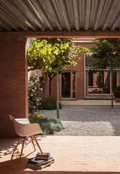 House 1014 in Barcelona by H Arquitectes. Two brick patios bracket the family home, offering a sheltered transition area from street accesses on either side of the block, while a further garden splits the space into two distinct halves – one for more private domestic activities, and another for entertainment.