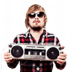Man wearing lumberjack shirt and sunglasses holding old school radio  by Urs Siedentop