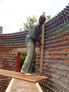 """Nineteen-year old mason, Yahaya Musa, checks a wall of made of sand-filled plastic bottles in the village of Sabon Yelwa. Sitting on 58-square metres, the two-bedroom bungalow looks like an ordinary home.  """"…the nearly-complete home is bullet and fireproof, earthquake resistant, and maintains a comfortable interior temperature of 64 degrees fahrenheit year round!…"""" ~Inhabitat"""