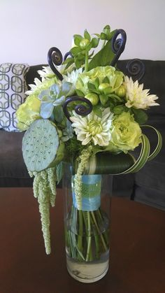 Green bouquet with fresh lotus pods and fiddle head fern curls.