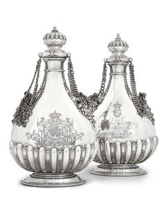 KING CHRISTIAN IX OF DENMARK'S SILVER WEDDING-GIFT A PAIR OF VICTORIAN MASSIVE SILVER PILGRIM-FLASKS MARK OF ROBERT GARRARD, LONDON, 1866 Each on spreading stepped oval foot, the lower part of the pear-shaped body applied with flutes, the shoulders applied with acanthus foliage and two vine wreathed Bacchic masks, hung with heavy chains, the domed gadrooned cover with baluster finial, each body later engraved on one side with a presentation inscription beneath 'C' cypher with Danish Royal…