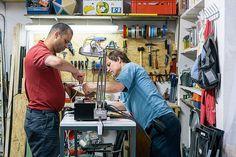 Zwei Männer schrauben gemeinsam in der Werkstatt.