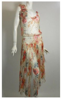 """Silk chiffon 1920s dress dotted with prong set rhinestones boasting a """"tattered"""" bouquet of flowers at shoulders."""