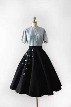 Wonderful black felt circle skirt from the 1950s. This skirt has a fitted waistline, a full circle skirt, rhinestone studded 3D stars along the side in blue and matching blue trim along the bottom of skirt. *blouse is sold separately!