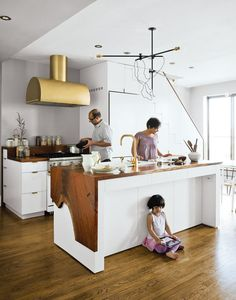 TOP BRASSThe Mandayam–Vohra family gathers under one of Workstead's signature three-arm chandeliers, shown here in its horizontal configuration in their Brooklyn kitchen with Custom cabinetry designed by Workstead and fabricated by the firm's go-to woodworker Bartenschlager. Wood and brass materials in a modern form make for a perfect rustic modern kitchen done right.    This originally appeared in Kitchens We Love: Part 2.