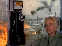 Melanie seeks shelter in a phone booth. A bird has just attacked a man at the gas station, causing him to spill gas, then a man lit a cigar. As the fire spreads, a man driving is attacked by birds and causes a crash. The firefighters lose control of a hose, spraying wildly at the phone booth.  A man covered in blood runs into the glass, a bird biting at his face. Just when you think it can't get any crazier, birds fly right into the phone booth, breaking the glass, giving Melanie nowhere to…