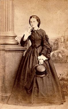 Carte de visite a woman in hoop-skirt, bodice with pagoda sleeves ca 1864  Adams St. Louis, Mo. Tax stamp on back.