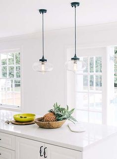 Industrial hanging pendant lights over the white granite composite counter on the kitchen island in this modern, all-white kitchen. Love the hints of tropical appeal!