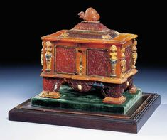 AN ENAMELED AND GOLD-MOUNTED AMBER CASKET Circle of Georg Schreiber (active 1616-43) and later, the mounts circa 1870 Of architectural form, the body decorated with panels carved in relief with scrolling foliage, fruit and fantastical grotesque beasts, with half-length busts of men and woman above pilasters and volutes, the hinged lid surmounted by an amber snail, with elaborate pierced bracket feet  --  Christie's