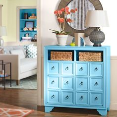 An upcycled dresser in a striking blue carries a fresh color palette between rooms. Accessories like an allen + roth™ framed mirror, a bronze lamp, a coral rug, and a painted terra-cotta pot and saucer complement the look.