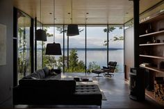 MW Works Architecture+Design        Nestled into a forested slope along the eastern edge of the Case Inlet, this small retreat opens to a western view of the Olympic Mountains and the Puget Sound. Anchored by a weathered cedar clad bedroom wing, a bold concrete cantilever projects the living and dining into the dense forest and toward the view.