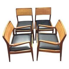 Set of four Jens Risom dining chairs. Two armchairs and two side chairs. The upholstery has been updated to a sleek black leather.