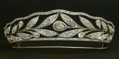 Diamond wreath tiara by Cartier, designed as two laurel leaf fronds interspersed with pear-shaped diamond 'berries', with a large central pear-shaped diamond and lines of diamonds at the top and bottom. Circa 1905.