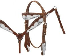 "$99.00 Showman ® Headstall and breast collar set featuring white hair-on cowhide with scalloped leather overlay with basket weave tooling. This double stitched medium leather headstall and breast collar set feature scallop cut leather overlay on white hair-on cowhide that is accented with basket weave tooling. Wide browband, cheeks and breast collar are accented with flower studs and crystal rhinestone crossed guns conchos. Headstall comes with 5/8"" x7' leather split reins."