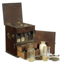 A medicine chest, English, late 18th century, the mahogany case with hinged lid opening to fitted interior with seven bottles and set of scales with weights, hinged door at the front opening to four further bottles and two powder drawers, when closed 9 1/2in (24cm) high