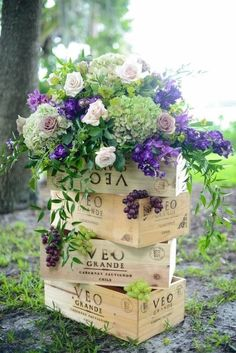 Overflowing bouquet of white, green and purple flowers in wine crates, with some grapes hanging around