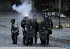 Riot police clash with opponents of Venezuela's Nicolas Maduro during a protest in Caracas