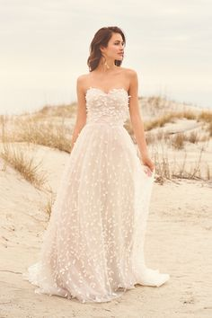 Soft romance is apparent in this sweetheart A-line gown with 3D flower petals. The tulle skirt with chapel length train is romantic and flirty.