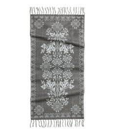 Rectangular, woven cotton rug with a printed pattern at front. Fringe on short sides.