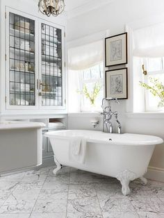Marvelous Master Bath  Traditional materials in soft hues are punctuated by white and black accents in this restful retreat. Richly veined marble tile, dark picture frames, and a claw-foot tub contribute to the room's regal appeal. Armoire doors crafted from old leaded-glass windows blend storage and beauty.
