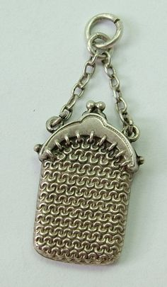 An Edwardian c1905 silver hollow charm of a chain mail purse with a chain strap.