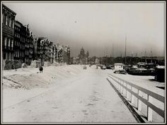1941. A view of a snow-covererd Prins Hendrikkade in Amsterdam. The Prins Hendrikkade runs from the Singelgracht along Central Station via the Waalseiland and Rapenburg east to the Kattenburgerplein. Famous buildings on the street include Victoria Hotel at the corner of Damrak, St. Nicholas Church at the beginning of the Zeedijk, Schreierstoren at the Geldersekade and the to Grand Hotel Amrâth converted Scheepvaarthuis. #amsterdam #1941 #PrinsHendrikkade