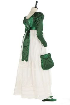 A green satin and whitework ensemble, circa 1820 The spencer bodice in two shades of green satin, with puffed mancherons, trimmed in blonde silk lace, with matching waist belt, reticule with cut steel button closure and chain; pumps labelled 'Rimmevaux, Rue de la Ferme des Mathurins, Paris' Kerry Taylor Auctions