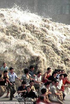 Spectators flee as huge waves of the Qiantangjiang River approach in east Chinas Zhejiang Province Sunday, Sept. 8, 2002. - Credit: AP Photo/Zhan Xiadong, XINHUA