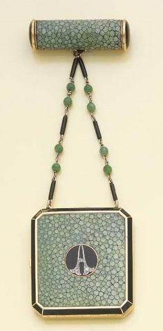 VINTAGE GREEN ART DECO JADE, ONYX AND ENAMEL VANITY CASE COMPACT embellished with onyx, small rose-cut diamonds, opening to reveal a mirror and compartment, a lipstick holder attached to chains accented with black enamel and jadeite jade beads, mounted in yellow gold, circa 1925. Signed Robert Linzeler Paris.