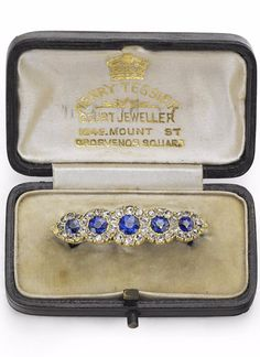 A Victorian sapphire and diamond bar brooch. Set with a graduated row of circular-cut sapphires, each surrounded by a frame of rose-cut diamonds, width 35mm, the sapphires estimated to weigh approximately 1.51cts in total