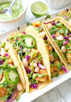 Roasted Cauliflower Tacos with Spicy Avocado Lime Crema. VEGAN and can be gluten-free with GF tortillas. Crispy + Spicy + Savory + Lime-y with a tangy avocado lime crema. YUM! From The Glowing Fridge. #vegan #tacos #healthy
