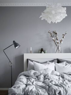 Don't you just want to jump right into this bed? The frilly Ikea Krusning lamp and cotton plant stems add just a light feminine touch.