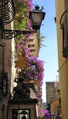 Taormina, Sicily, Italy...love the iron balconies twined with flowering vines!