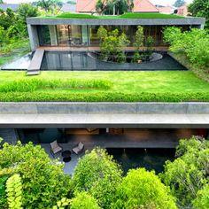 """""""The Wall House"""" autorstwa pracowni the FARM łączy główną jadalnię i przestrzenie dzienne poprzez wyłożone granitem patio, na którym rośnie sześć wierzb sięgających okrągłego otworu w stropie. Na dachu krawędź otworu jest otoczona wodą, która przechodzi w bujny, zielony dach łączący kondygnacje powyżej. http://www.sztuka-krajobrazu.pl/345/slajdy/ogrody-nowoczesne-scalone-z-architektura"""