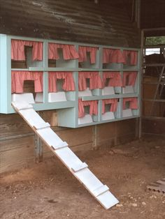My Aqua chicken nesting boxes with red checked curtains and tin roof. Repurposed from old upper kitchen cabinet.