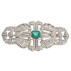 Emerald Diamond White Gold Brooch. This brooch is an exquisite example of a piece of Art Deco jewelry. This pin features 288 round pave set brilliant diamonds, which average SI1 clarity and J color. The estimated carat weight is 4.03. There is one bezel set square emerald of good quality, weighing 1.85 carats. c 2000s so it's Art Deco style