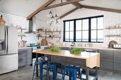 The open kitchen at DIY Network Ultimate Retreat 2017 has an industrial style that highlights natural materials, including wood ceiling beams that pull the eye up and a custom center island that encourages good traffic flow.