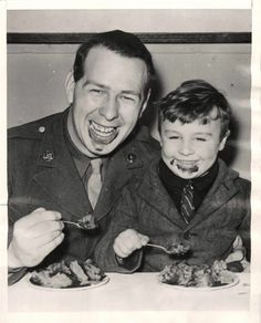 """1943- U.S. soldier eating ice cream with a little British boy at Christmas party given by troops of the USAAF Service Command for 100 English evacuees at a station """"somewhere"""" in England."""