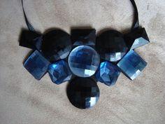 Maxi Colar confeccionado em base de feltro preto com aplicação de chatons em acrílico nas cores preta e azul marinho. Amarração com fita de gorgurão preta. R$59,00