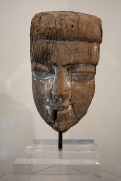 A wooden Egyptian mummy mask with bold, distinctive face