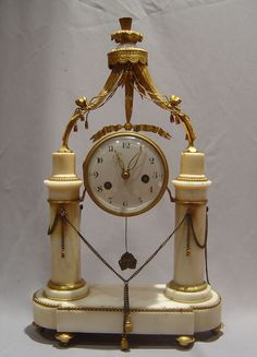 Antique Louis XVIth White Carrera Marble And Ormolu Mantel Clock Held Between Two Marble Columns With Ormolu Mounts Top And Bottom - France   c.1785