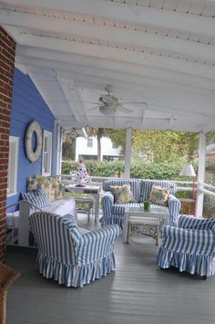 Porch with blue and white stripe covered arm chairs.