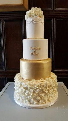 Gold, cream and ivory wedding cake with ruffles and monogram