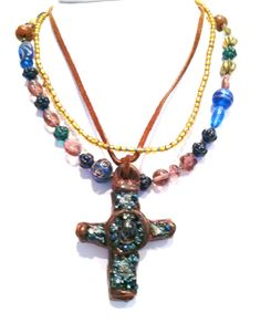 This three strand necklace is made of various shapes and colors of glass beads, lampwork beads, brass beads, leather, and a beautiful handmade