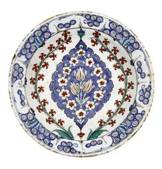 AN IZNIK POLYCHROME POTTERY DISH, TURKEY, LATE 16TH CENTURY of shallow round form, decorated in underglaze cobalt blue, green and relief red, featuring tulip buds within a floral border set in an almond-shaped frame, with two hyacinth stems on either side, the rim with a breaking wave design, the underside with small floral motifs 30cm. diam.