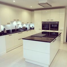 Wren Kitchens: Autograph Cream Gloss with polished Nero Absoluto granite tops - love the flush hob on the island. What do you think to the contrasted design?