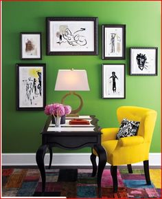 green wall with black and white pics and yellow chair
