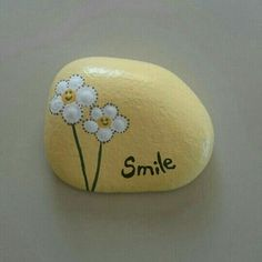 """Smile"" and flowers painted on a stone"